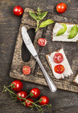Sandwiches with cream cheese, tomatoes and basil for healthy snack on rustic wooden cutting board, top view. Sandwiches with cream cheese, tomatoes and basil for stock photos