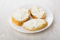 Sandwiches with curd cheese with greens in white plate on table Stock Photos