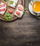 Sandwiches with curd cheese with parsley, cherry tomatoes and salmon on a cutting board and a cup tea with thyme  border ,place Royalty Free Stock Photo