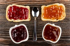 Sandwiches with currant jam, apricot jam, spoon, bowls with jam on table. Top view. Sandwiches with currant jam, apricot jam, teaspoon, bowls with jam on dark stock photos