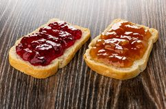 Sandwiches with currant jam and apricot jam on table. Sandwiches with currant jam and apricot jam on dark wooden table royalty free stock photos