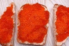 Sandwiches in de vorm van harten met rode zalmkaviaar en boter op roggebrood, hoogste mening royalty-vrije stock fotografie