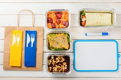 Sandwiches and dry erase board. Marker, a dry erase board, plastic flatware and a paper bag, nuts and dried fruit, cheese and lettuce sandwiches, plums royalty free stock image