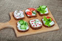Sandwiches with feta cheese and cucumber, tomato and radish. The Stock Photo