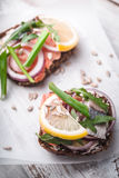 Sandwiches with fish and lemon on a white parchment Stock Photo