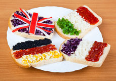 Sandwiches with flags of four countries. On plate Royalty Free Stock Photography