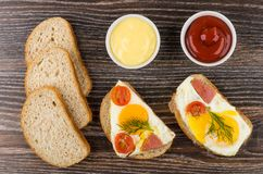 Sandwiches with fried egg, sausage, tomatoes, bread, ketchup and Stock Images