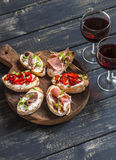 Sandwiches with goat cheese, anchovies, roasted peppers, ham and two glasses of red wine on a wooden rustic board. Stock Photography
