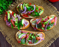 Sandwiches with greens, tomatoes, meat, salami on crispy bread Stock Images
