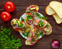 Sandwiches with greens, tomatoes, meat, salami on crispy bread on the table. Royalty Free Stock Image