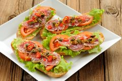 Sandwiches with ham, salad leaves, chili, tomatoes, capers, fren Royalty Free Stock Photos