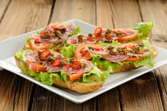 Sandwiches with ham, salad leaves, chili, tomatoes, capers, fren Stock Photography