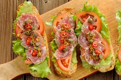 Sandwiches with ham, salad leaves, chili, tomatoes, capers, fren Stock Image