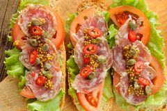 Sandwiches with ham, salad leaves, chili, tomatoes, capers, fren Royalty Free Stock Images