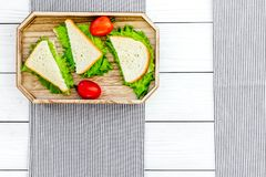 Sandwiches with lettuce and tomatoes for picnic on tablecloth on white wooden background top view copyspace Royalty Free Stock Photography