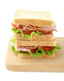 Sandwiches with lettuce,tomato,cold cuts on cutting board on white. Sandwiches with lettuce,tomato,cold cuts on white background on cutting board Royalty Free Stock Images