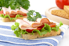 Sandwiches with lettuce,tomato,cold cuts on kitchen towel. Sandwiches with lettuce,tomato,cold cuts with parsley on kitchen towel Royalty Free Stock Image