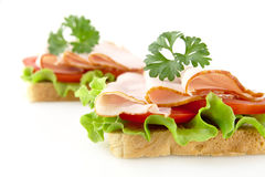 Sandwiches with lettuce,tomato,cold cuts with parsley on white. Sandwiches with lettuce,tomato,cold cuts on white background with parsley Royalty Free Stock Images