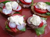 Sandwiches with mayonnaise. Fresh spring time sandwiches: bread, butter, lettuce, pork, tomato, radish and mayonnaise royalty free stock images
