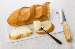 Sandwiches with melted cheese, bread on cutting board, knife. Sandwiches with sweet melted cheese, loaf of bread on cutting board, knife on wooden table stock images
