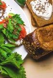 Sandwiches met avocado, forel en zure room, met kruidige dille wordt bestrooid die Selderiebladeren stock foto