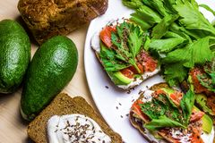 Sandwiches met avocado, forel en zure room, met kruidige dille wordt bestrooid die Selderiebladeren stock afbeeldingen