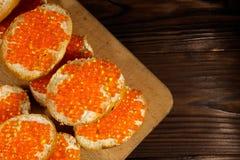 Sandwiches met boter en rode kaviaar op houten lijst Royalty-vrije Stock Foto