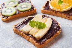 Sandwiches met chocoladedeeg en diverse vruchten op een grijze lijst Hoogste mening Concepten heerlijk ontbijt royalty-vrije stock foto