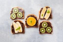 Sandwiches met chocoladedeeg en diverse vruchten op een grijze lijst Hoogste mening Concepten heerlijk ontbijt stock afbeeldingen
