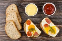 Sandwiches met gebraden ei, worst, tomaten, brood, ketchup en stock afbeeldingen