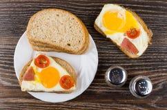Sandwiches met gebraden ei, worst, tomaten, brood, zout en pe royalty-vrije stock foto's