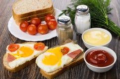 Sandwiches met gebraden ei, worst, tomaten, brood, zout, peppe stock afbeelding