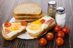 Sandwiches met gebraden ei, worst, tomaten, brood, zout, peppe royalty-vrije stock fotografie