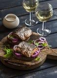 Sandwiches met geroosterde vissen en snelle ingelegde uien en twee glazen witte wijn Royalty-vrije Stock Fotografie