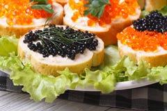 Sandwiches met rode en zwarte kaviaar op sla stock afbeeldingen