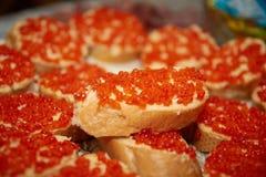 Sandwiches met rode kaviaar op een feestlijst stock foto's