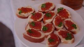 Sandwiches met rode kaviaar op een plaat stock footage