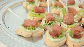 Sandwiches met roomkaas, blad van sla en een stuk van ham op catering stock video
