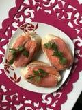 Sandwiches met zalm die, met greens worden verfraaid Lig op een plaat op een rood servet Royalty-vrije Stock Afbeelding