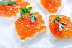 Sandwiches met zalm rode kaviaar en kruiden op wit servet Sluit omhoog beeld met selectieve nadruk Royalty-vrije Stock Fotografie