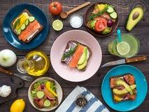 Sandwiches met zalm, zwart brood, groenten in platen en een glas limonade op de lijst Stock Afbeeldingen