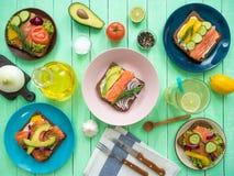 Sandwiches met zalm, zwart brood, groenten in platen en een glas limonade op de lijst Royalty-vrije Stock Fotografie