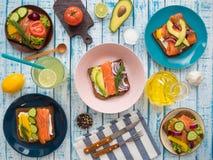 Sandwiches met zalm, zwart brood, groenten in platen en een glas limonade op de lijst Royalty-vrije Stock Foto's