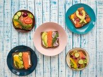 Sandwiches met zalm, zwarte brood en groenten in platen op de lijst Stock Afbeelding