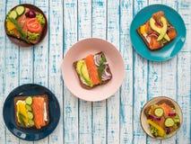 Sandwiches met zalm, zwarte brood en groenten in platen op de lijst Stock Foto's