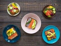 Sandwiches met zalm, zwarte brood en groenten in platen op de lijst Royalty-vrije Stock Foto's