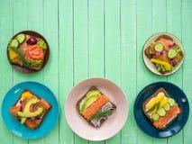 Sandwiches met zalm, zwarte brood en groenten in platen op de lijst Royalty-vrije Stock Foto
