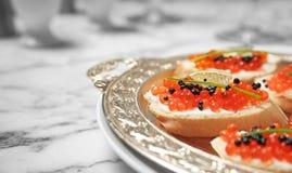 Sandwiches met zwarte en rode kaviaar op dienblad Stock Foto