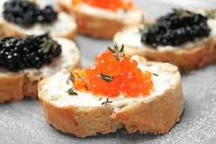 Sandwiches met zwarte en rode kaviaar op lijst Stock Afbeelding