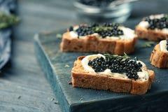 Sandwiches met zwarte kaviaar en boter Stock Foto
